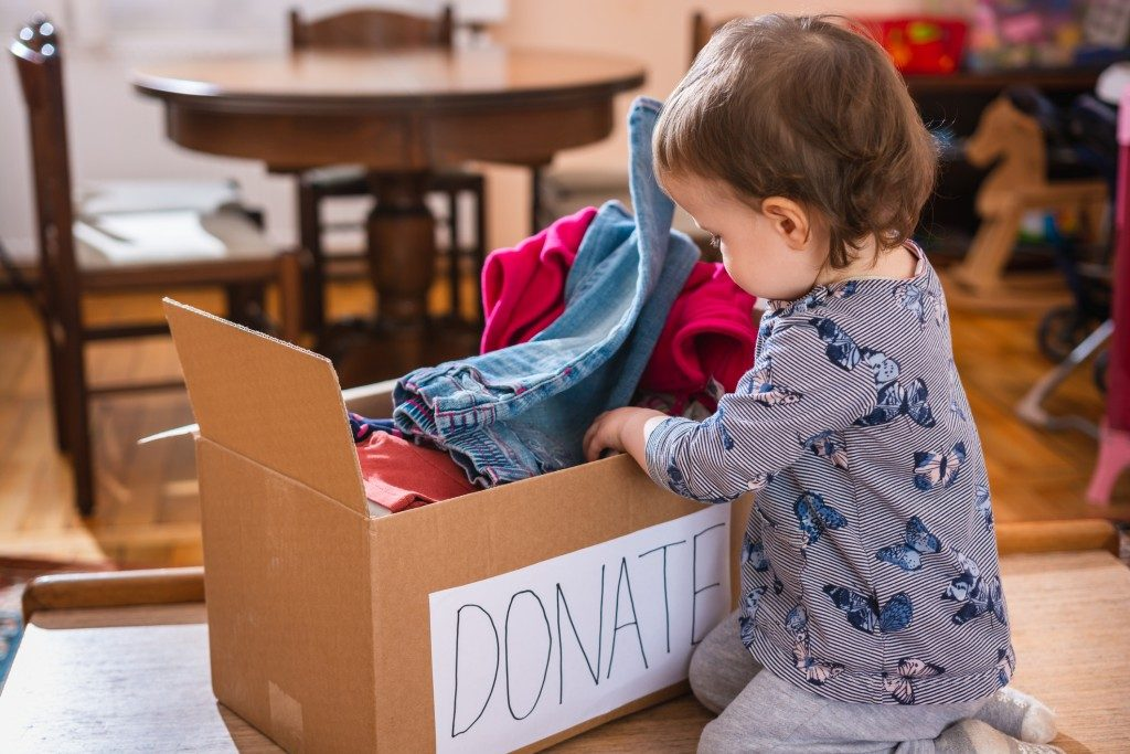 Baby inspecting a box of donated clothes