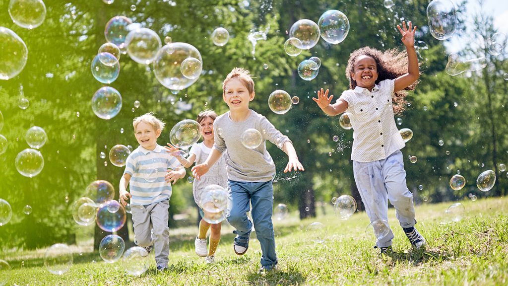Kids playing with bubbles outside