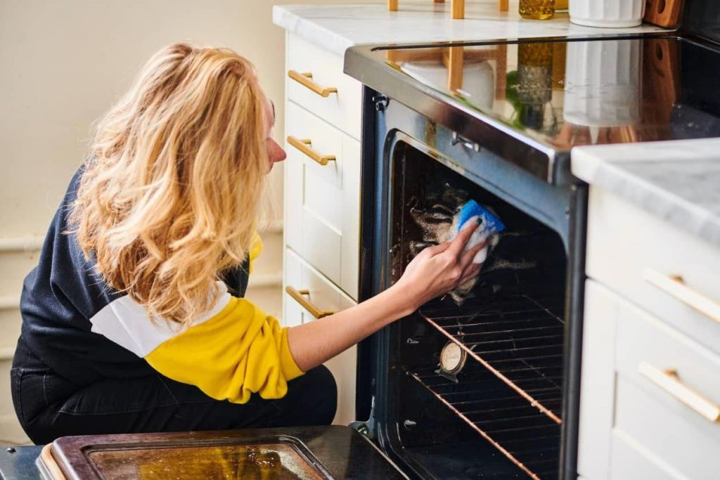 woman cleaning out oven