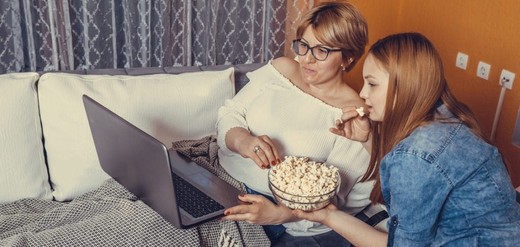 Teen and her mom watching a movie